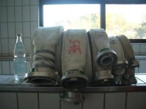Fünf aufgerollte Druckschläuche unterschiedlicher Grössen. Von links: Druckschlauch Grösse A, B, C 52, C 42 und D. Als Größenvergleich steht ganz links eine Mineralwasserflasche.